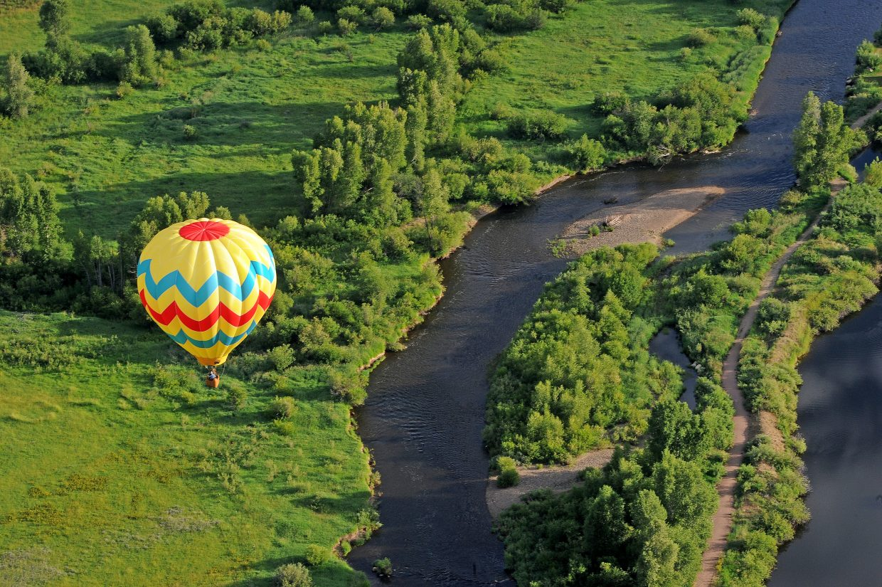 A hot air balloon hovers above the Yampa River on Friday morning.