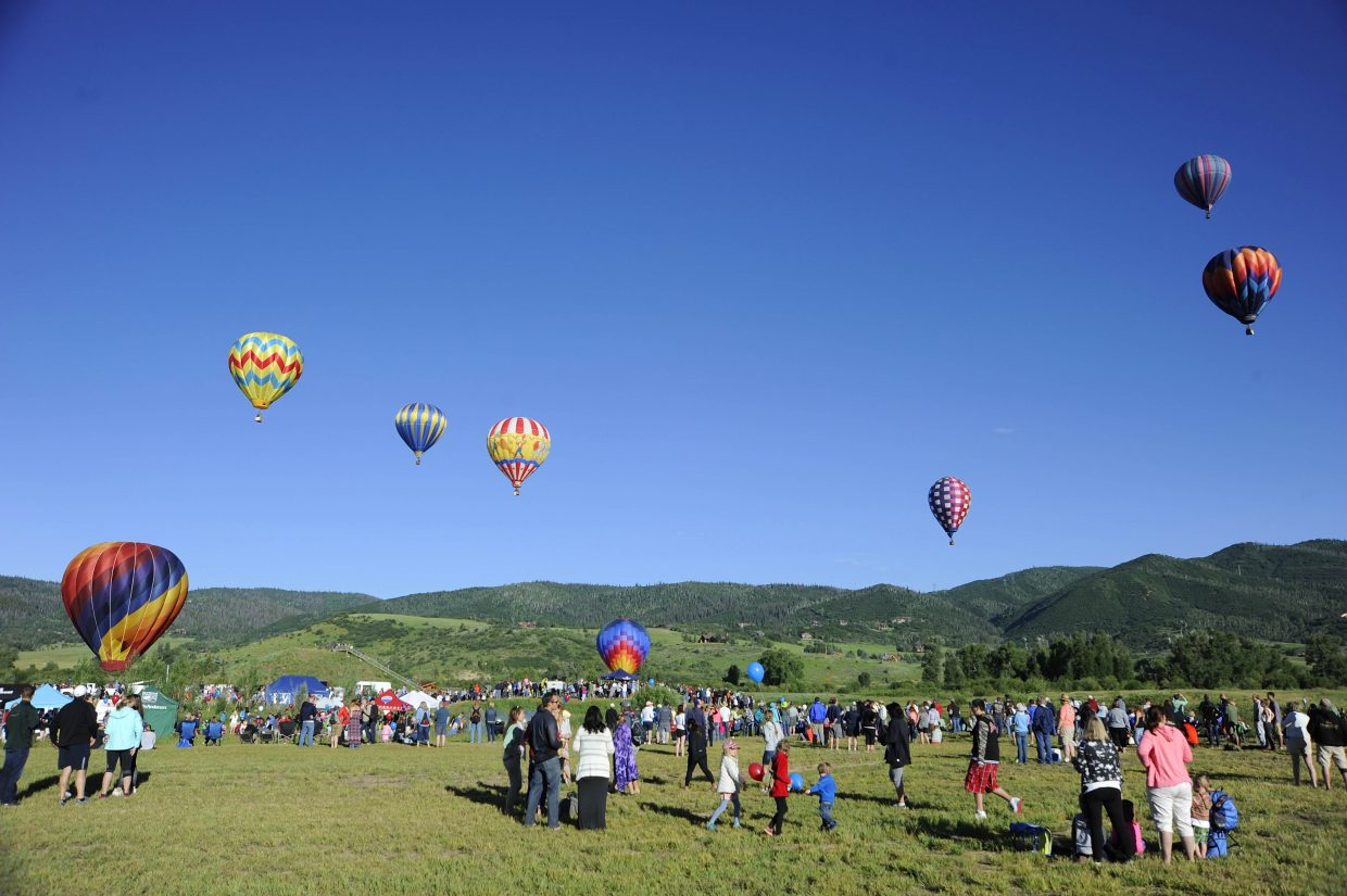 Spectators watch balloons fly over the Yampa Valley from Bald Eagle Lake during Saturday's Balloon Rodeo.