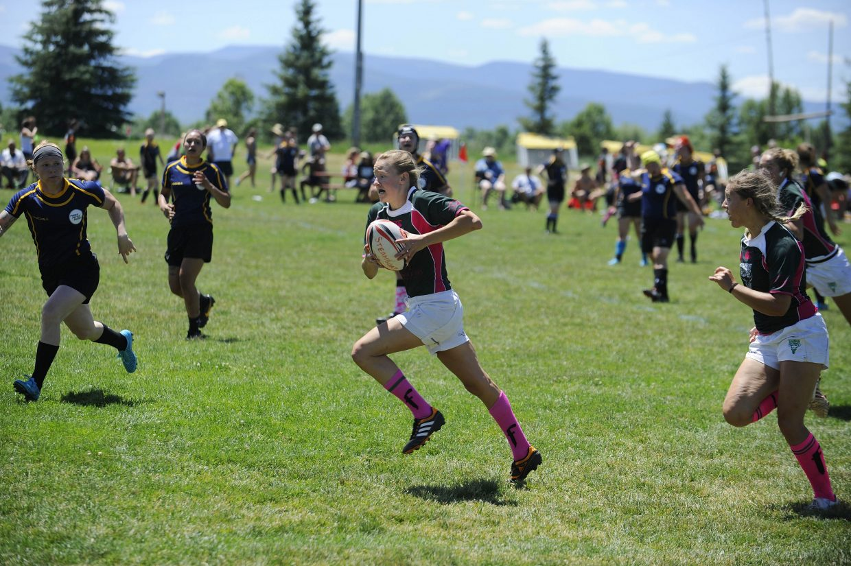 Steamboat Springs Rugby Football Club player Kate Hunt runs the ball down the pitch during Saturday's Cowpie Classic game against Colorado Springs.