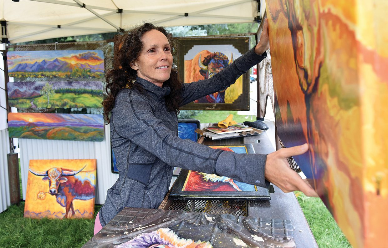 Mixed media artist Meg Harper hangs her work inside her tent at West Lincoln Park Friday afternoon. Harper, who creates art out of reclaimed material, is one of 125 artist in town for this year's Art in the Park. The festival will open up at 9 a.m. Saturday and runs through the weekend.