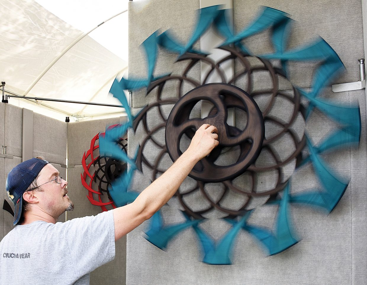 Artist Ryan Kvande sets up his Spunwheel booth Friday afternoon at West Lincoln Park. Kvande, who makes optical illusion sculptures is among 125 artists who will take part in this year's event, which opens Saturday morning at 9 a.m.