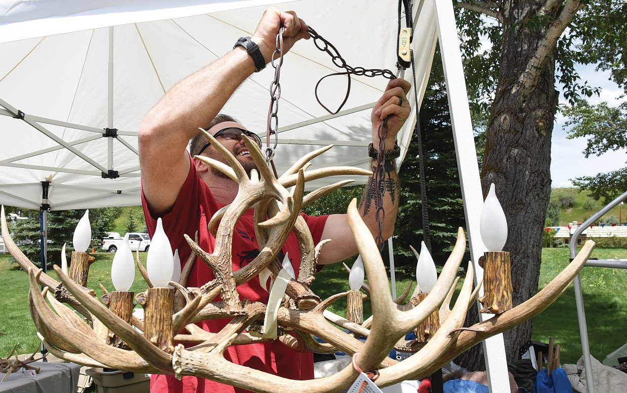 Jeff Spiker, of Rocky Mountain Antler Works in Golden, hangs one of his pieces Friday inside his tent, located at West Lincoln Park. Spiker is one of 125 artists taking part in this year's Art in the Park, which will open Saturday morning at 9 a.m.