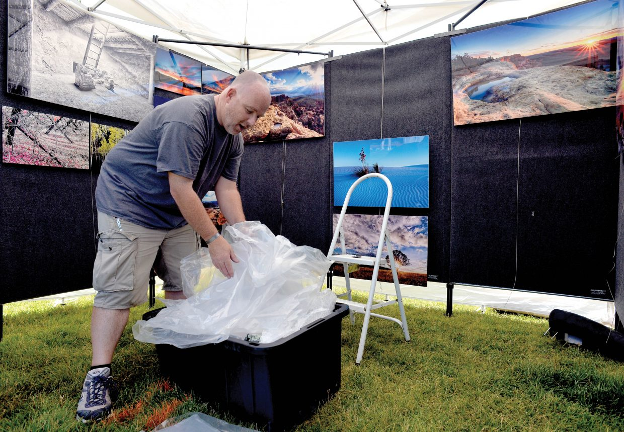 New Mexico photographer Scott McCarmick sets up his booth, Mas Beyondo, for this year's Art in the Park at West Lincoln Park in downtown Steamboat Springs. The arts, crafts and music festival will run from 9 a.m. until 5 p.m. Saturday and from 9 a.m. until 4 p.m. Sunday. It features artisans from around the country.