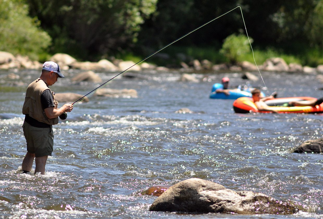 A flyfisherman tries to land trout in the Yampa River as tubers go by. Some commercial outfitters and community members are calling for more regulations of private tubers.