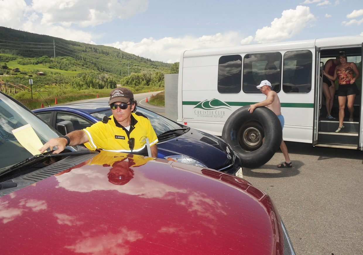 Steamboat Springs Community Service Officer Scott Schaffer puts a ticket on a vehicle parked illegally at the Rotary Park parking area while tubers get off a shuttle bus during tubing season. Paid parking at popular river put ins is one of the ideas that have been suggested to generate revenue for more enforcement on the river.