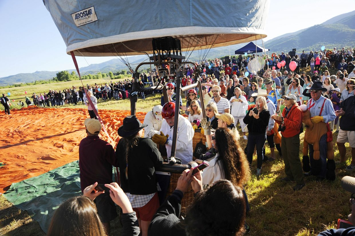 People watch the Western Spirit hand-painted balloon inflate during the 34th annual Hot Air Balloon Rodeo on Saturday at Bald Eagle Lake.