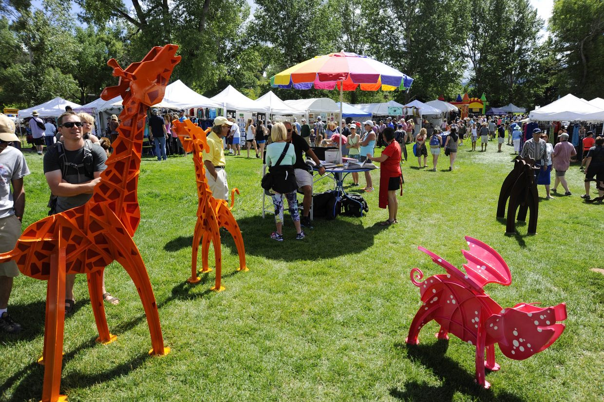 People check out art for sale during the Art in the Park Event on Saturday at West Lincoln Park. The event continues Sunday from 9 a.m. to 4 p.m.