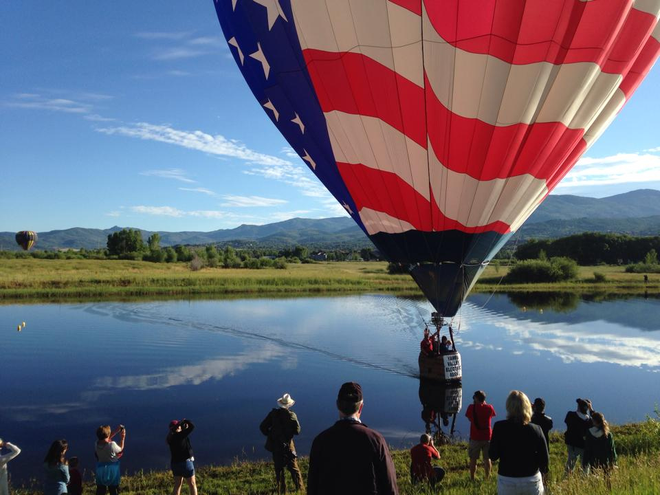 A balloon skims across Bald Eagle Lake toward the early morning crowd of spectators Saturday.