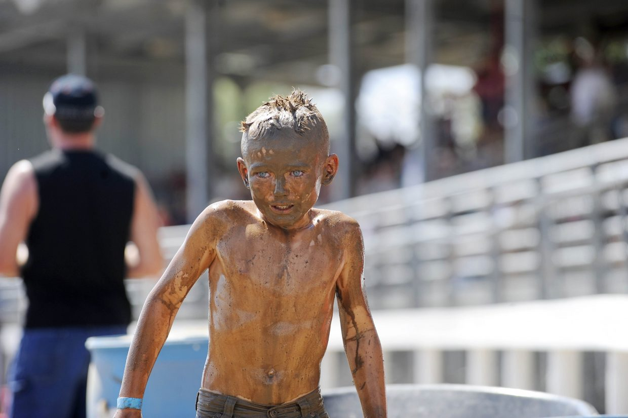 Dorian Hotchkiss, 9, comes out of the mud pit after the Kids Mud Surfing competition Saturday at the Routt County RedneX Games in Hayden.
