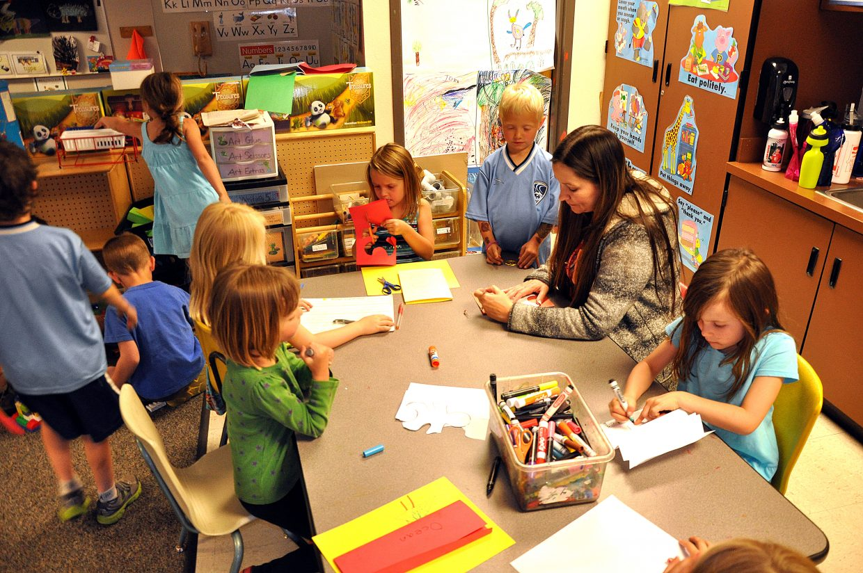 Teacher Carol Harris works with kindergarten students on an art project in 2013. Colorado Governor Jared Polis is pushing for the state to fully fund kindergarten.