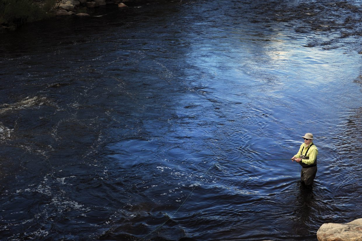 Gabe Dreuhl, of Austin, Texas, takes on the blue waters of the Yampa River in Steamboat Springs looking to land a trout.