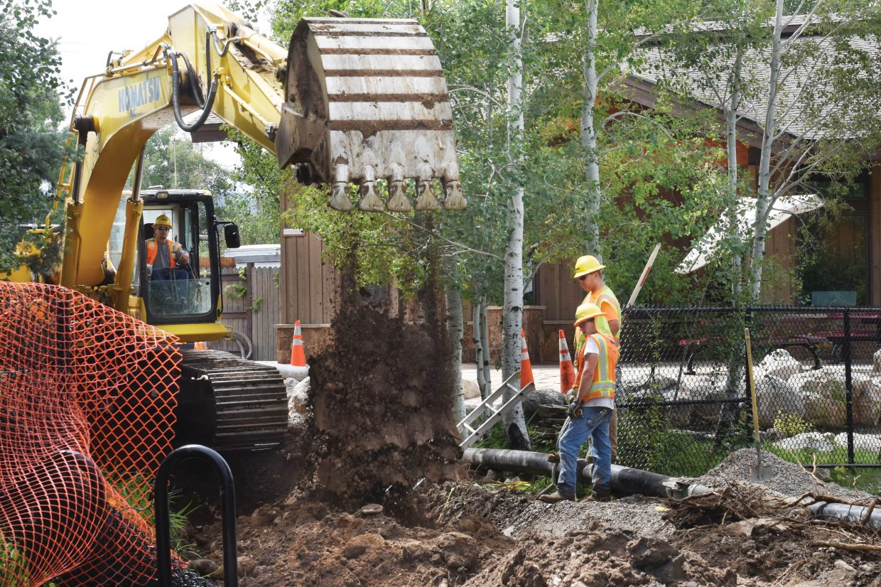 Construction workers use an excavator as part of a project to upgrade the water and sewer lines leading to the Fish Creek Mobile home park. The project has temporarily closed the Yampa River Core Trail, but crews are hoping to have the trail open by the end of the week.
