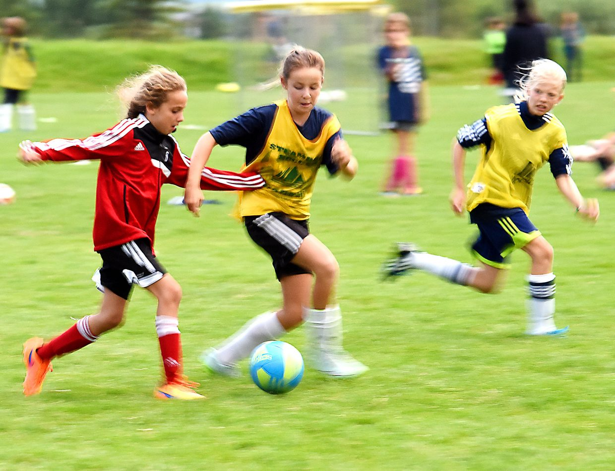 Jocelyn Lohmeyer, 9, left, and Ella Frusciano, 11, fight for the ball Tuesday night during a soccer camp in Steamboat Springs. This week's camp included nearly 200 athletes, and a similar camp last week included about the same number of players. Practice turns to play starting Thursday as the annual Steamboat Mountain Soccer Tournament kicks off with 160 teams.