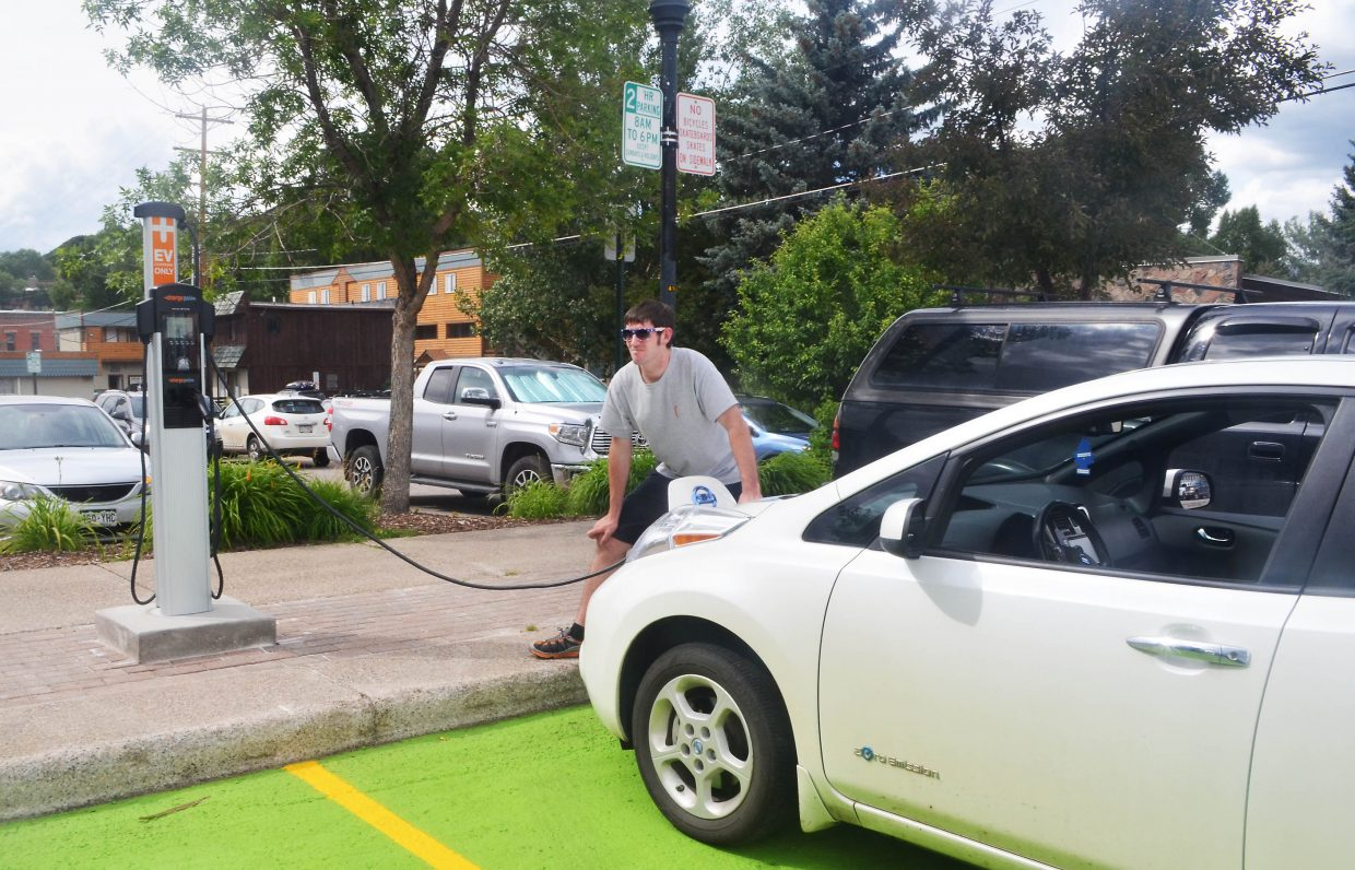 Matt Troeger demonstrates the use of the city of Steamboat Springs' new Charge Point level II dual pedestal charging station on his family's Nissan Leaf on 10th Street Wednesday. The use of the charger is free to owners of electric vehicles who have an account with Charge Point, and the station can accommodate two cars at a time for up to four hours of use.