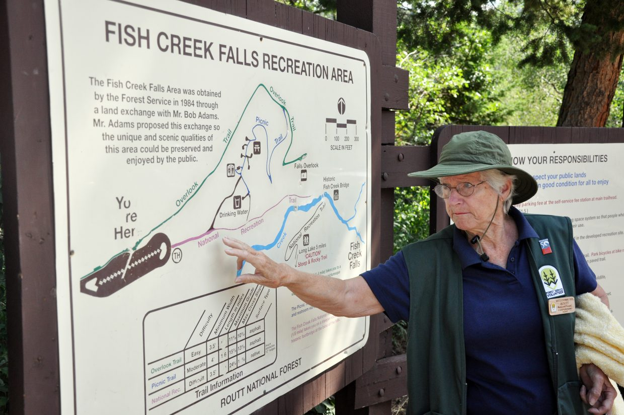 Nina Lowe uses a map to show visitors to Fish Creek Falls where they can hike to Wednesday afternoon. This is Lowe's third summer helping visitors at the falls.