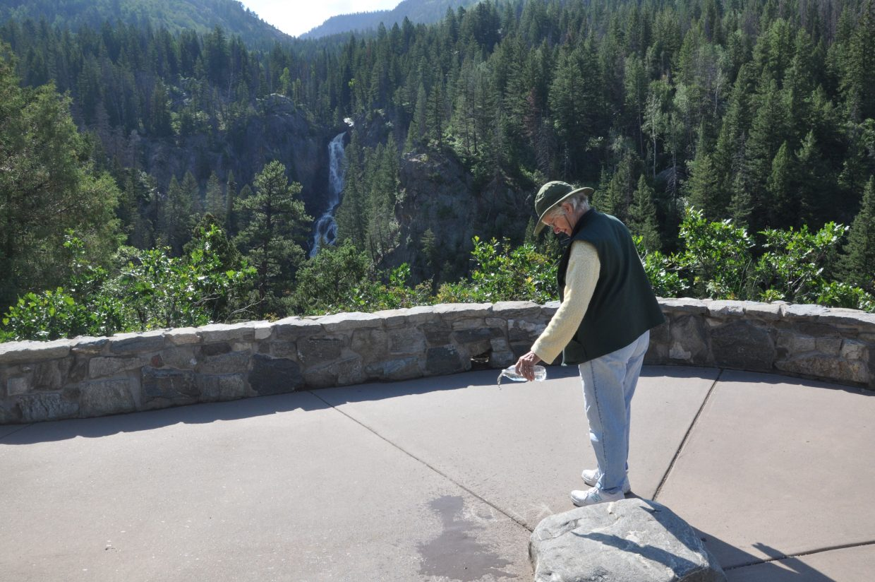 Nina Lowe washes away some chalk art from an overlook at Fish Creek Falls.