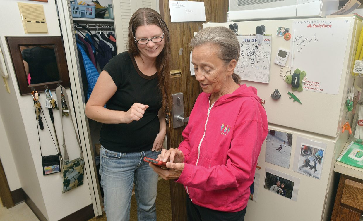 Sue Carpenter gets a helping hand from Ski Town Computing's Amy Johnson on Friday morning at the senior citizen apartments in downtown Steamboat Springs. Ski Town Computing stopped by to help residents with any problems they were having with phones, tablets and computers.