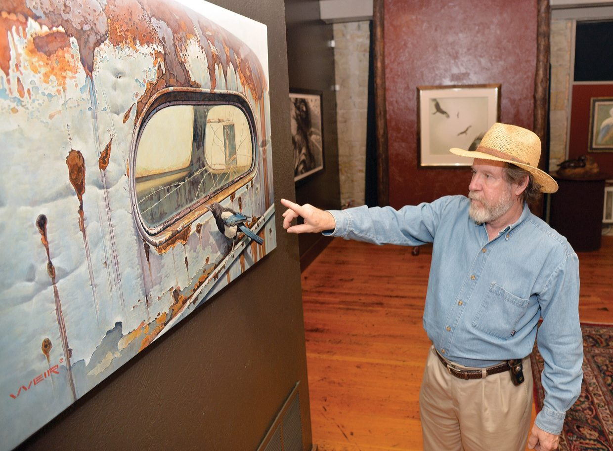 The Steamboat Arts Museum's Richard Galusha explains one of the many paintings in the latest show, Birds in Art, before the show's opening at the downtown arts center. The show, which took more than three years to arrange, is a mixture of paintings and sculptures of an Avery nature.