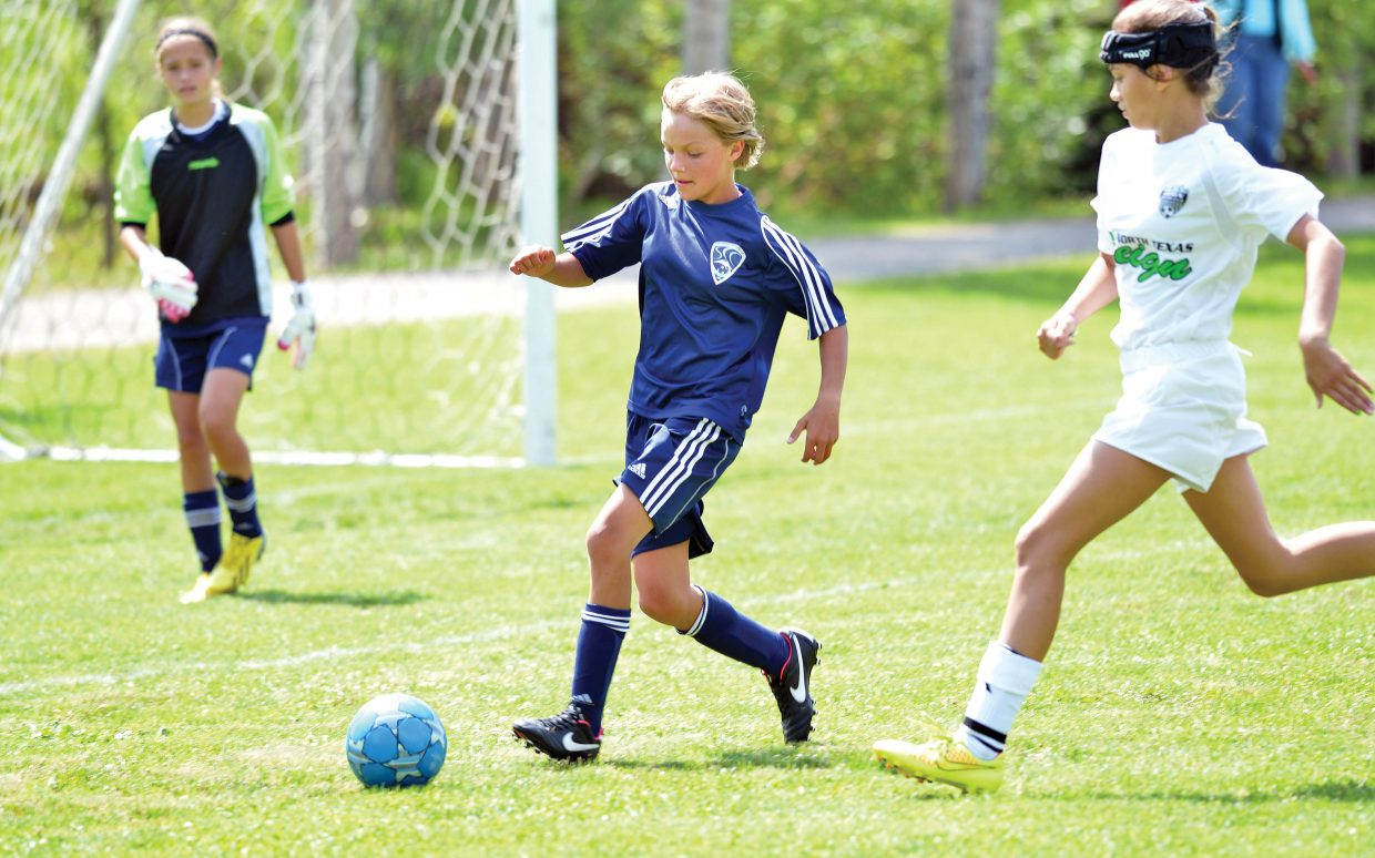 Shelby McCannon, of the Steamboat Springs U12 white team, works to clear the ball Friday during the first day of the Steamboat Mountain Soccer Tournament. The Steamboat girls, just one of many teams playing in this weekend's tournament, lost the game to the visiting NTX Reign O2 girls from Texas.