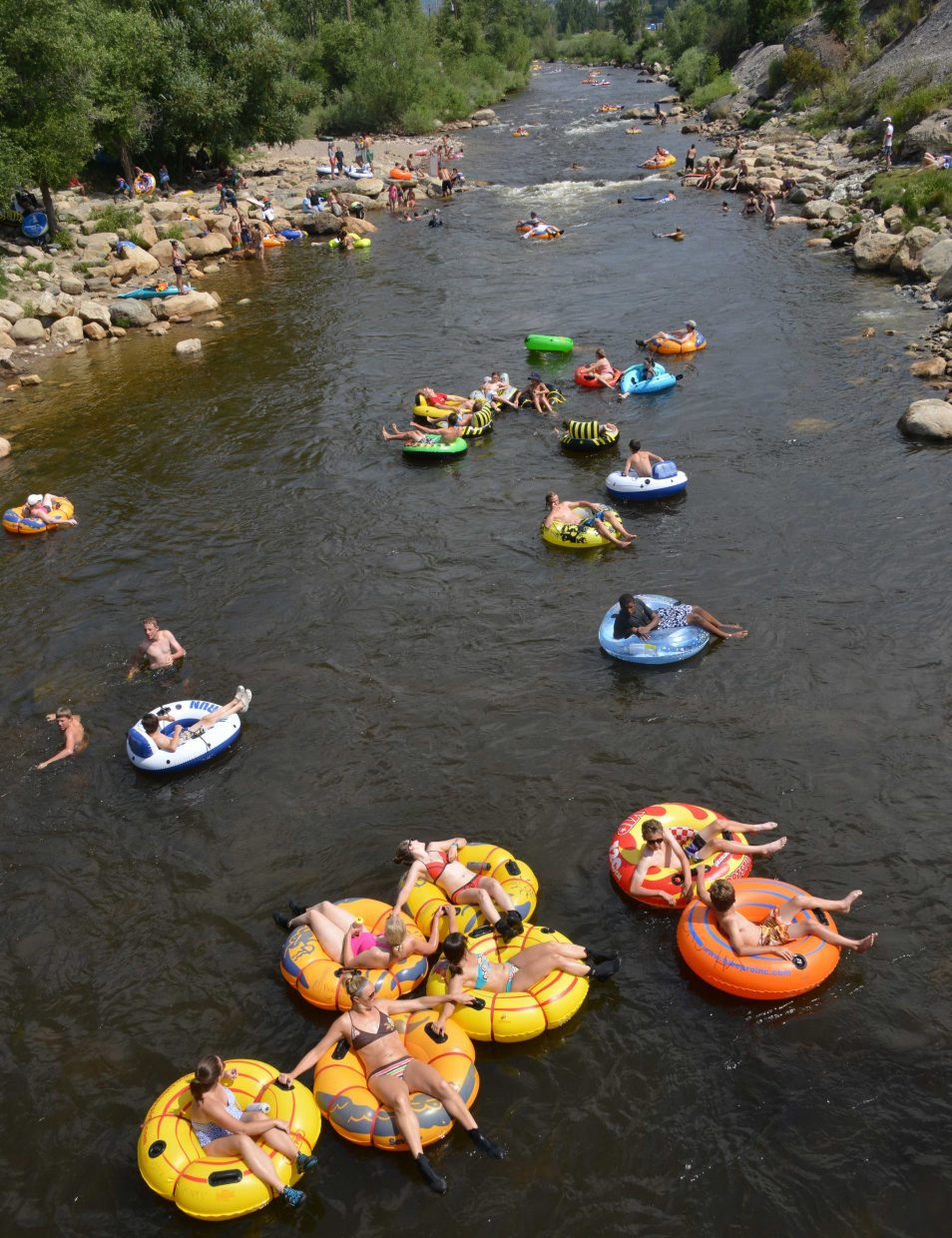 Tubers ride down the Yampa River through Charlie's Hole in downtown Steamboat Springs on a busy Sunday.