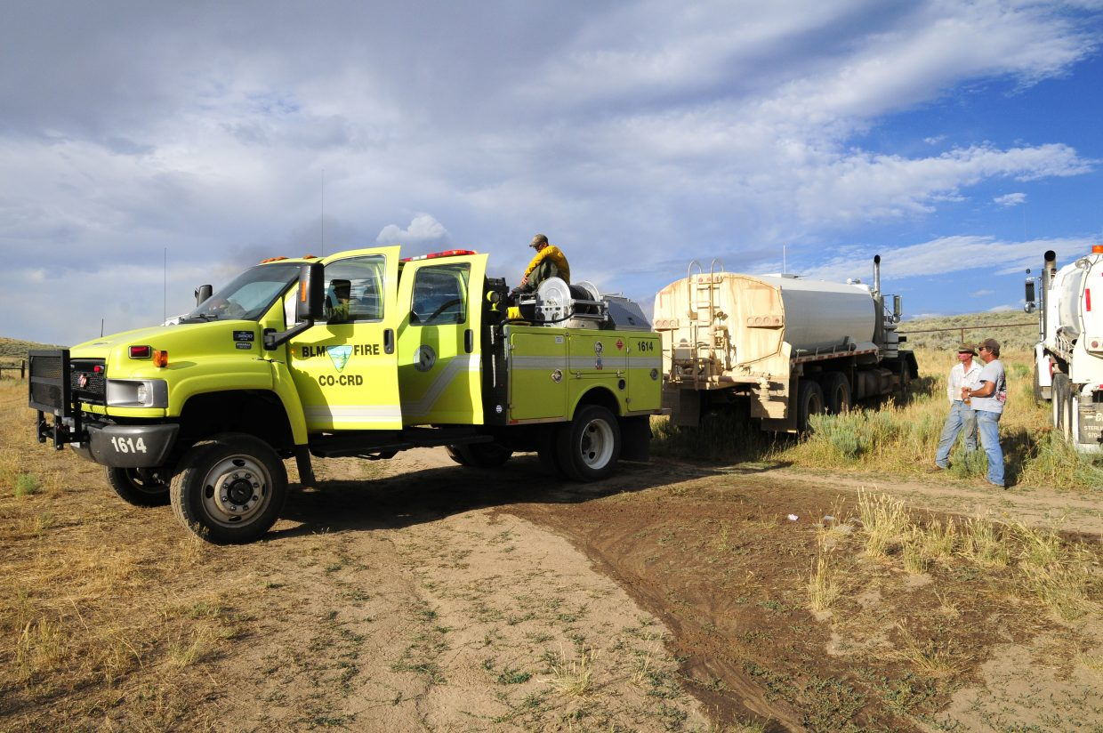 A BLM fire truck refills from a Moffat County water truck before going back out to tackle the Alkali fire Wednesday.