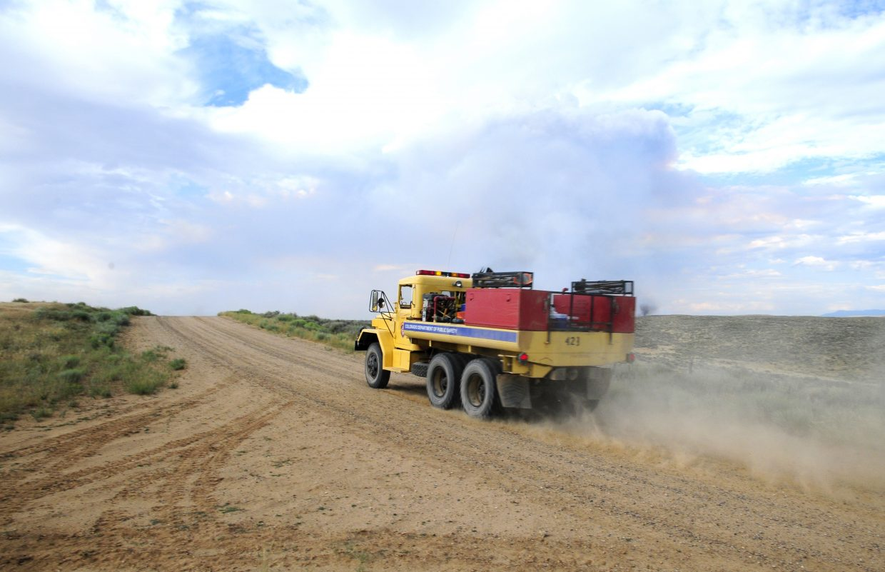A Colorado Department of Public Safety truck rushes towards the edge of the fire along Moffat County Road 6 Wednesday evening.