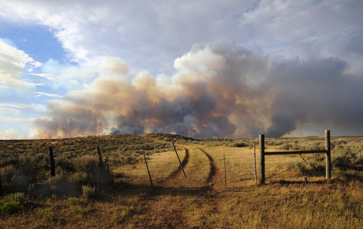 The Alkali fire sends plumes of smoke into the air north of Moffat County Road 8.