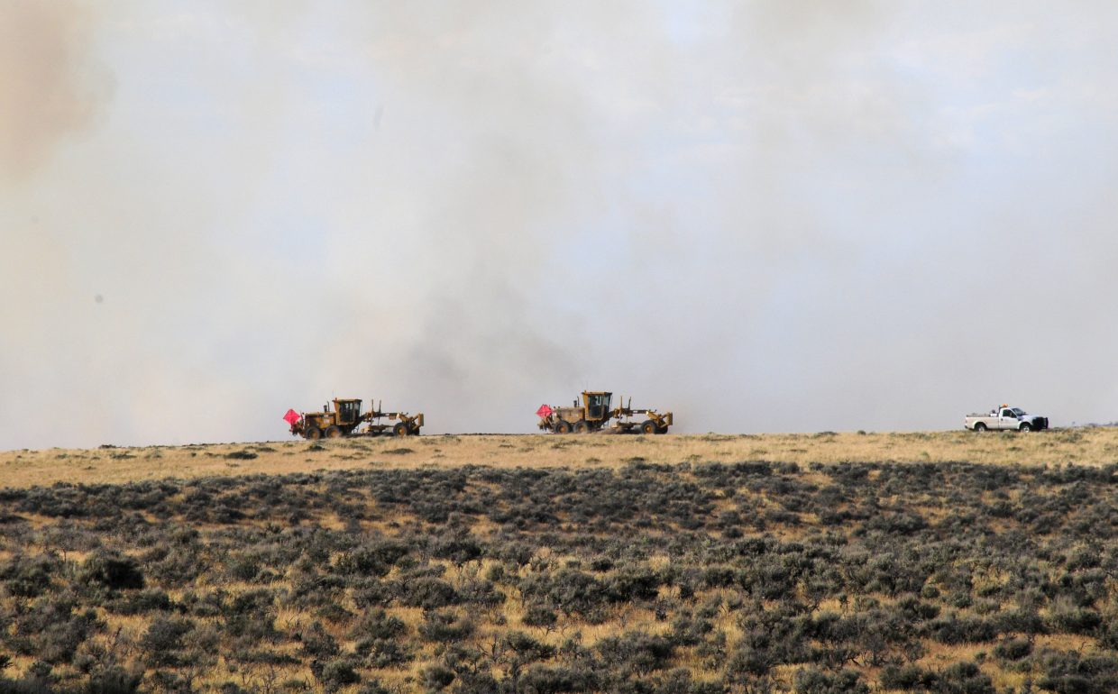 Two graders work Wednesday to create a fireline along the southern edge of the Alkali fire to keep the flames from spreading.