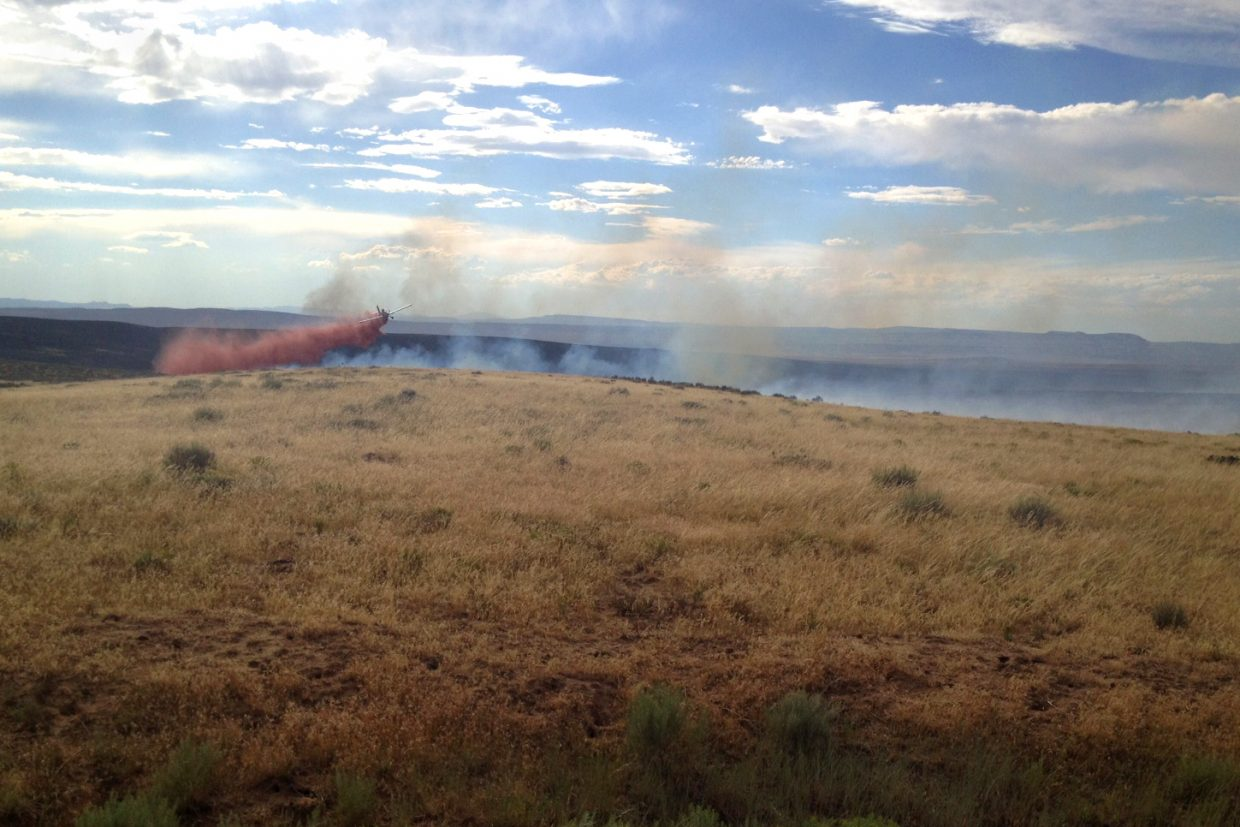 A plane drops retardant on the southern edge of the Alkali fire late Wednesday afternoon.