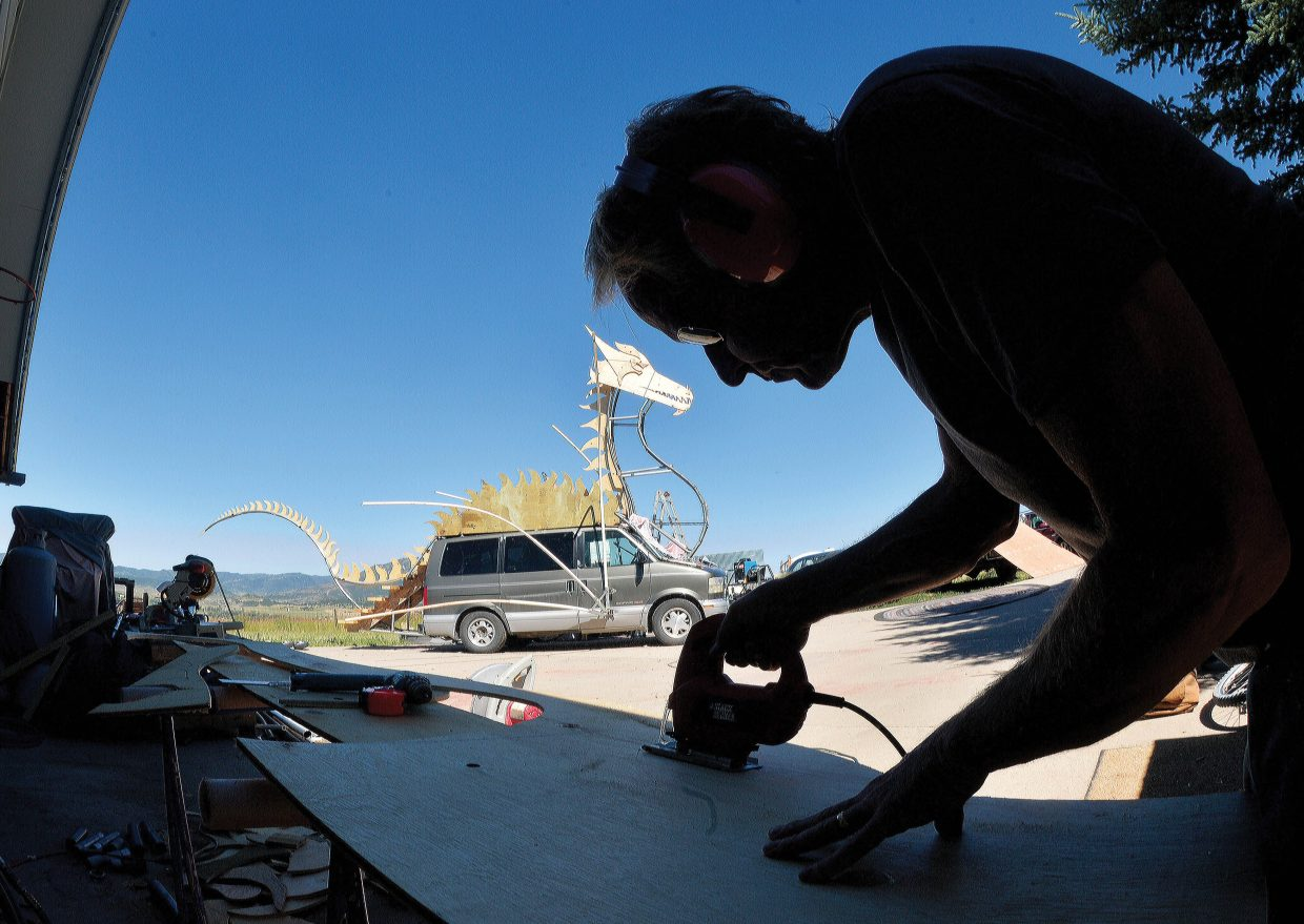 Charlie Holthausen uses a power saw to cut out a platform for a tank on the mutant car that he is building for this year's Burning Man Festival in Nevada. Holthausen is eager to bring his new dragon back to some of Steamboat Springs biggest celebrations.