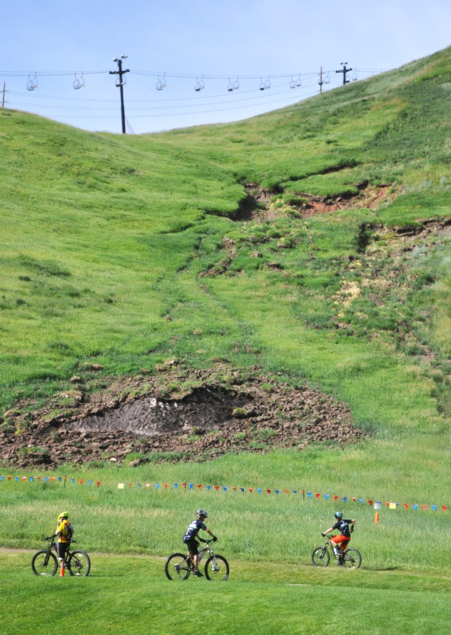 Cyclists pedal around the base of Howelsen Hill as damage from a significant spring mudslide lingers on the steep face of the hill. The city of Steamboat Springs is anticipating having to spend in the neighborhood of $35,000 to $45,000 to repair the damage from the slide.
