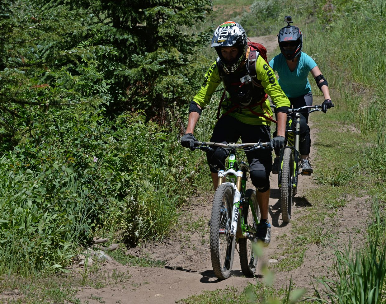 Nicole Miller follows Steamboat Bike Park instructor Andrew Burns down the Wrangler Gulch trail.