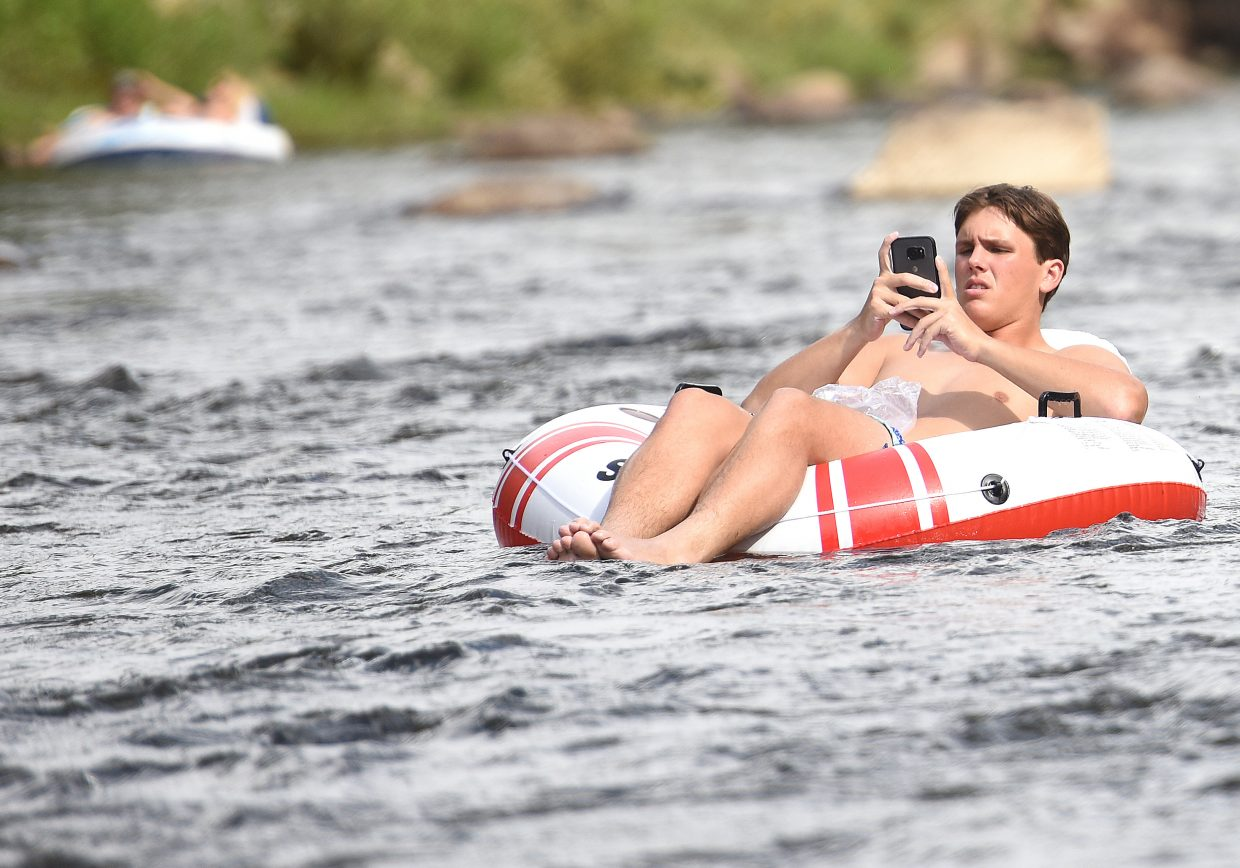 Filming and floating: Jake Gitter, from New Orleans, pulled his phone from a protective plastic bag Sunday to take some video as he floated down the Yampa River in downtown Steamboat Springs. Dark clouds rolled in with a few strokes of lightning elsewhere in the valley on Sunday, but that didn't stop a slow but steady stream of people from taking a float down the river.