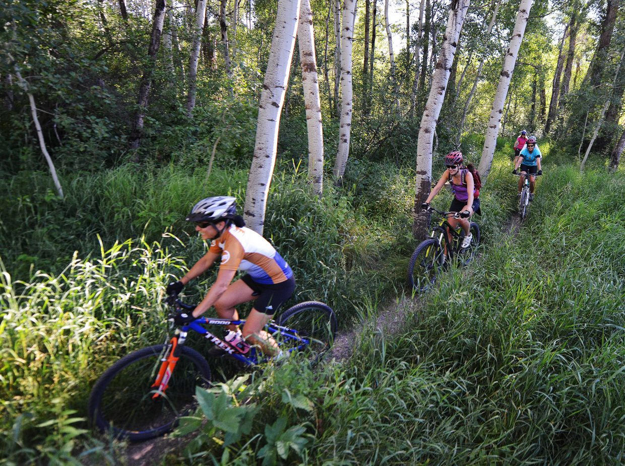 Riders in Steamboat Ski & Bike Kare's Tuesday night mountain bike clinic head down Spring Creek Trail on Tuesday evening. The classes alternate between group rides and skills clinics and often draw more than 50 women.