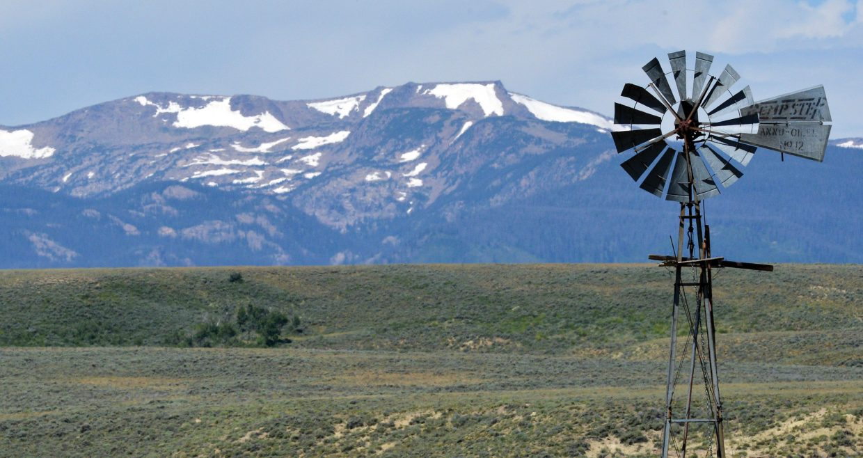 The snow-covered peaks provide the backdrop for a windmill between Steamboat Springs and Walden.