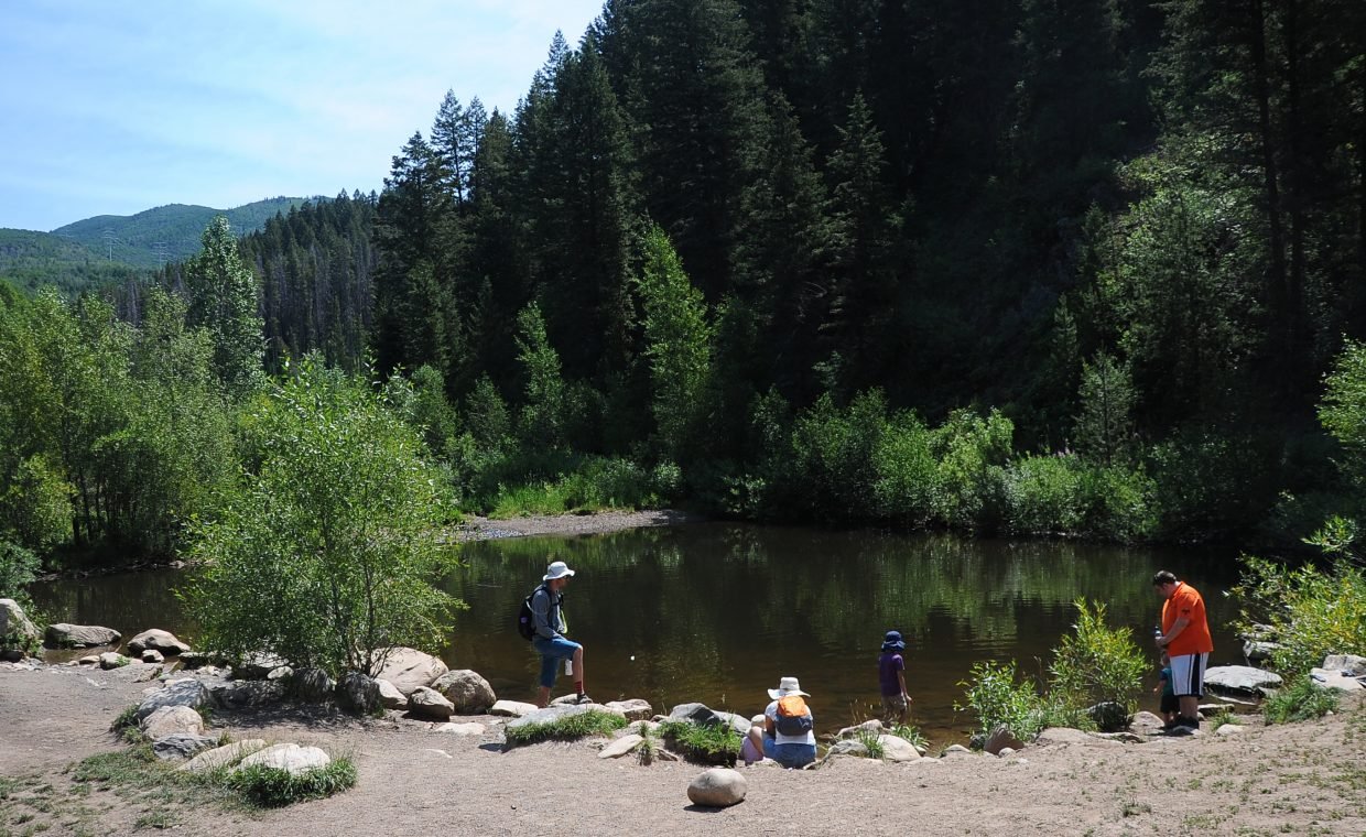 Families enjoy one of the ponds fed by Spring Creek on Monday. The Upper Spring Creek Dam is more than a century old and is in need of costly repairs or replacement.