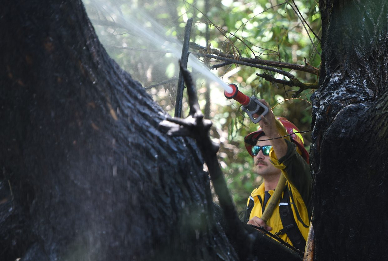 Steamboat Springs firefighter Dane Visnick sprays down a charred tree along the banks of Spring Creek next to Memorial Park on Monday in downtown Steamboat Springs. Firefighters were called concerning smoke and fire rolling out of the trees along Second Street near Steamboat Springs High School. Several volunteers, with the help of a fire extinguisher, knocked the fire down by the time crews arrived, and there were no remaining visible flames. Crews remained on the scene to ensure there would be no re-ignition and to begin investigating the cause of the short-lived blaze.