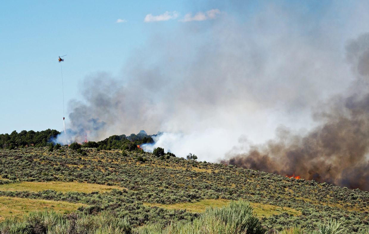 A helicopter dops water on the Milk Fire in southern Moffat County.