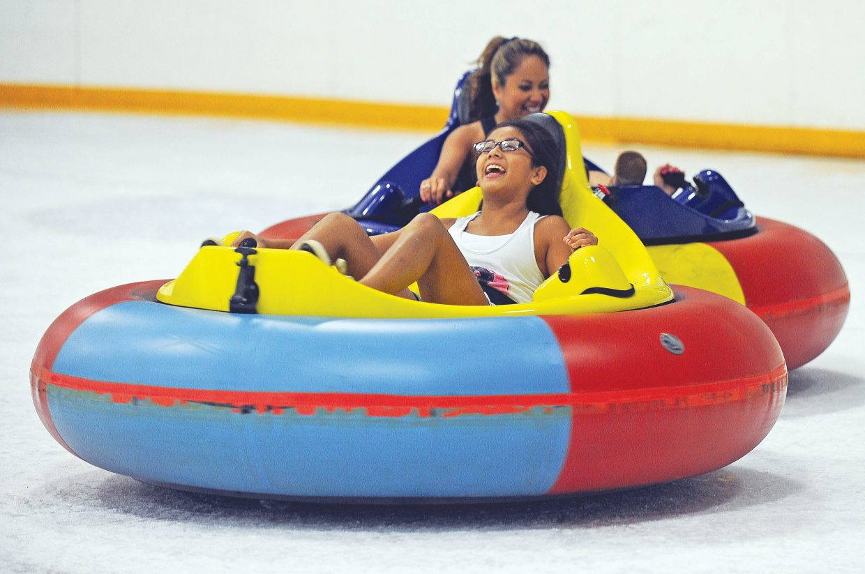 Thu Tran laughs after getting bumped by Yung Tran during a session of bumper cars on ice at the Howelsen Hill Ice Arena Monday afternoon.