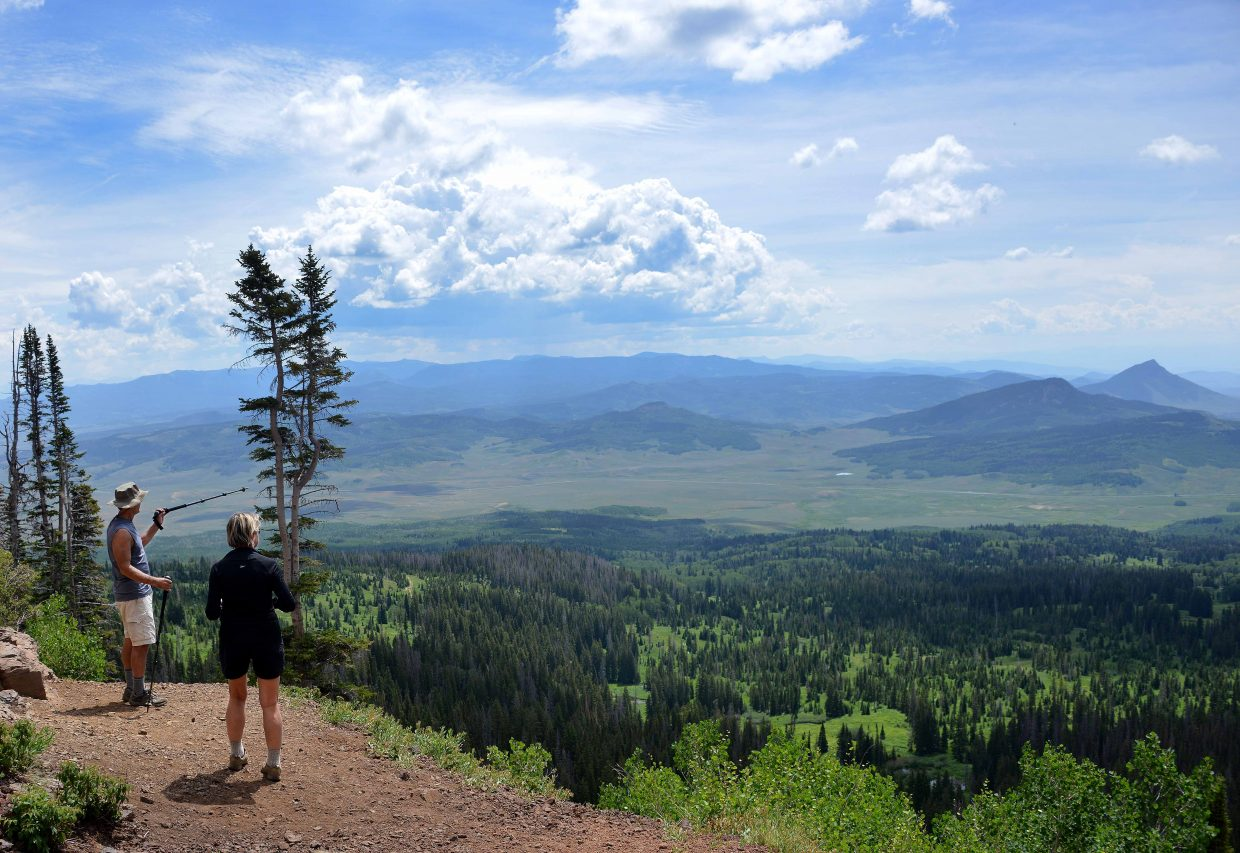 A pair of hikers soak in the view from the top of Rabbit Ears Peak on Monday afternoon. Plenty of hikers took to the trail to one of the area's signature peaks and fields of wildflowers lined the way. The hike is available off U.S. Highway 40 near Dumont Lake, and down Forest Service Road 291.