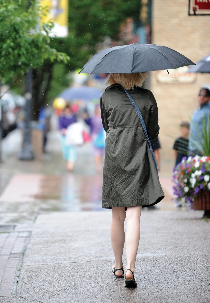 Jessica Miller uses an umbrella as shelter from the rain as she walks down Lincoln Avenue Tuesday afternoon.