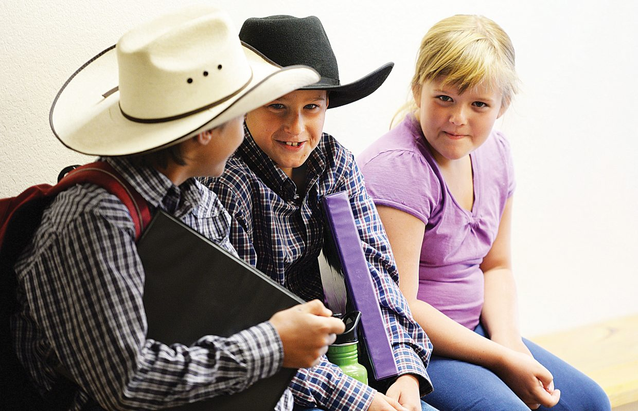 Tim Bedell, middle, visits with Colt Larkin, left, and his sister, Jessica Bedell (who was there to keep her brother company), while waiting to be interviewed as part of the 4-H shooting programs at Soroco High School. The children were taking part in the Routt County Fair's annual exhibit day, at which judges interview the students and score them on how well they've met the requirements of the 4-H program. The young agriculture students must complete a book outlining what they accomplished during the summer and display quality interviewing skills as judges test their knowledge. Exhibit Day always takes place before the start of the Routt County Fair, which runs Aug. 7-15 this year.