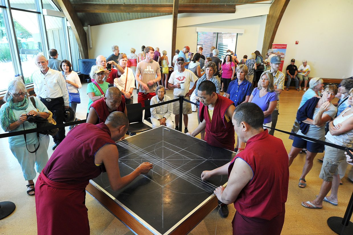 A crowd watches the visiting monks prepare to make the Mandala painting in Bud Werner Memorial Library.