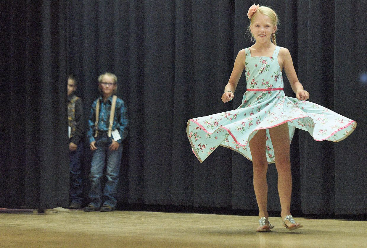 Alivia Warren, who was competing in the junior division, twirls on stage during the 4-H Fashion Revue Friday at Soroco High School. The show took place before the Routt County 4-H Exhibit Day awards ceremony.