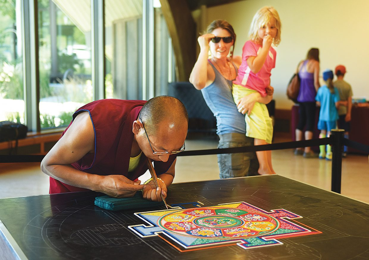 Tsering Phuntsok, of the Drepung Loseling Monastery, works to form a mandala image at the Bud Werner Memorial Library on Thursday afternoon. A small group of monks are working on the mandala, which is created with millions of grains of brightly colored grains of sand.