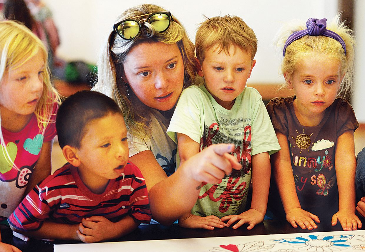 Kid's Kabin Preschoolers Micah Wettlaufer, Emmett Anzalone, teacher Crystal Brenegan, Bennett Creagan and Brooklynn Dyche check at the community mandala at the Bud Werner Library on Thursday afternoon. Each day the community can come in and work on the community mandala, which is made up of millions of grains of colored sand.