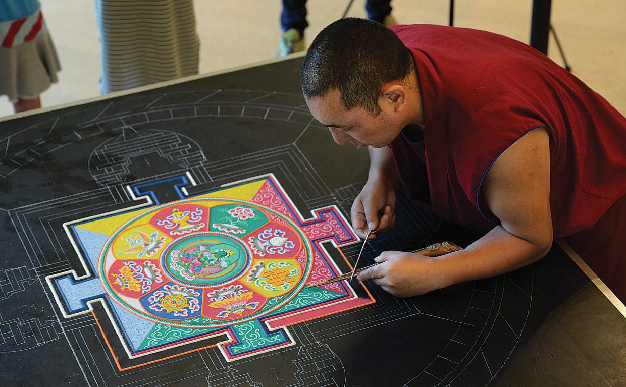Monk Tsering Dhargye, of the Drepung Loseling Monastery, works to form a mandala image at the Bud Werner Memorial Library on Thursday afternoon. A small group of monks are working on the mandala, which is created with millions of grains of brightly colored grains of sand.