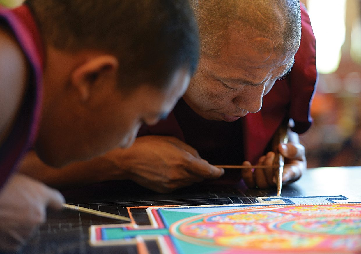 Monk Nyima Tsering Tamang, of the Drepung Loseling Monastery, works to form a mandala image at the Bud Werner Memorial Library on Thursday afternoon. A small group of monks are working on the mandala, which is created with millions of grains of brightly colored grains of sand.