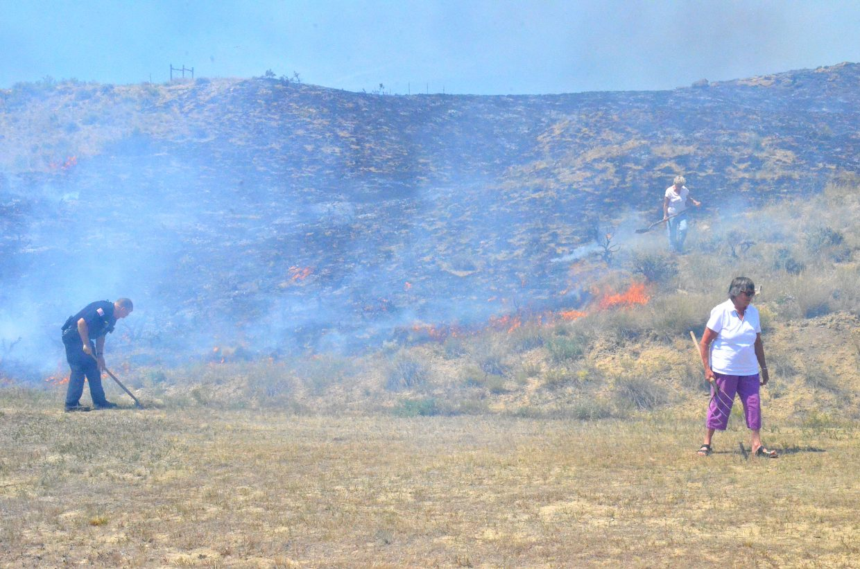 A law official and neighbors work to extinguish a wildland fire near the bypass in Craig Thursday afternoon.