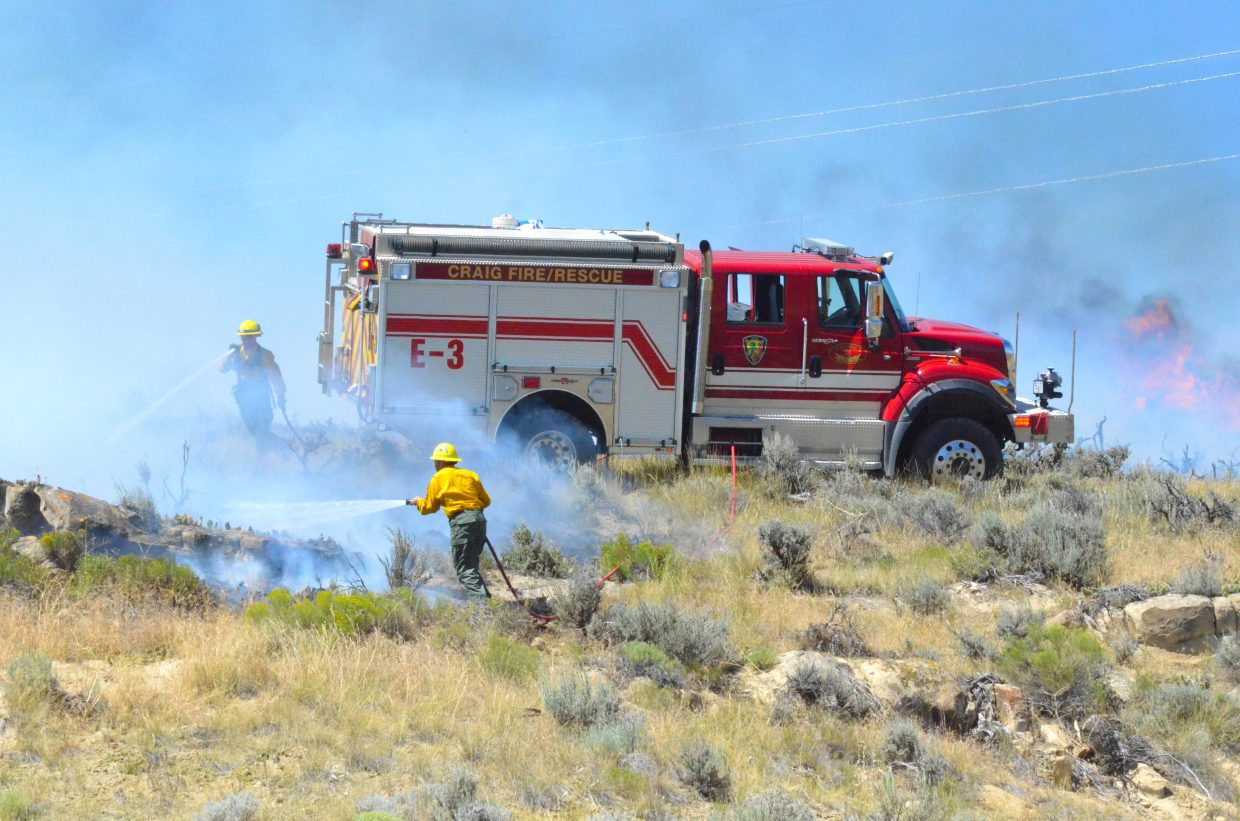 Firefighters work to extinguish flames Thursday afternoon at the bypass in Craig.